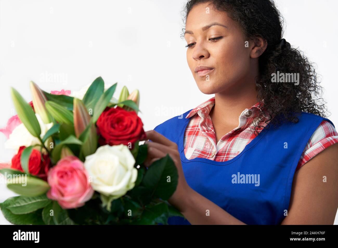 Floristería Femenina Arreglando El Ramo De Flores Y Rosas Contra El Fondo Blanco Foto de stock