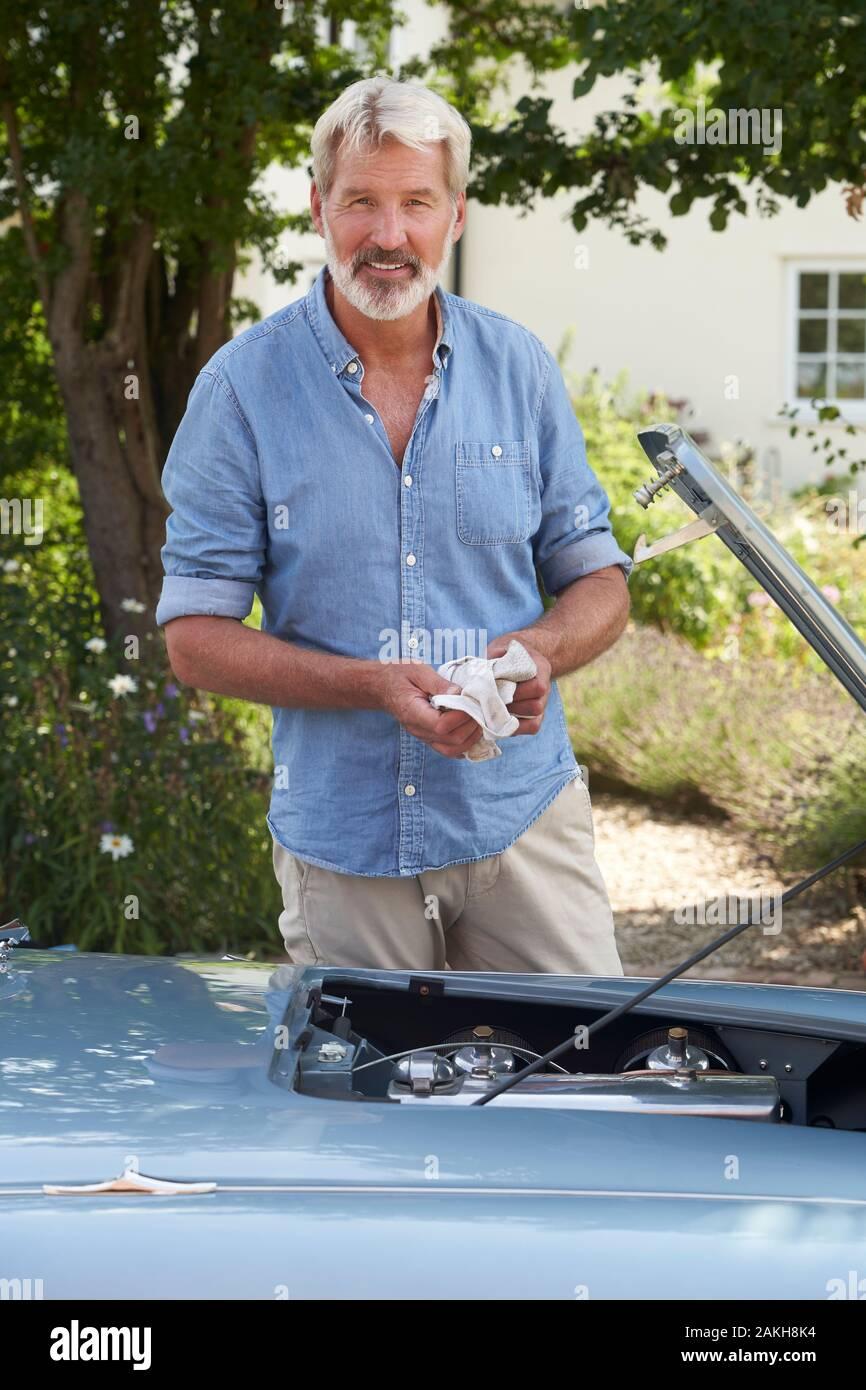 Retrato de hombre maduro, de trabajar en el motor bajo el capó de clásico restaurado del coche de los deportes al aire libre Foto de stock