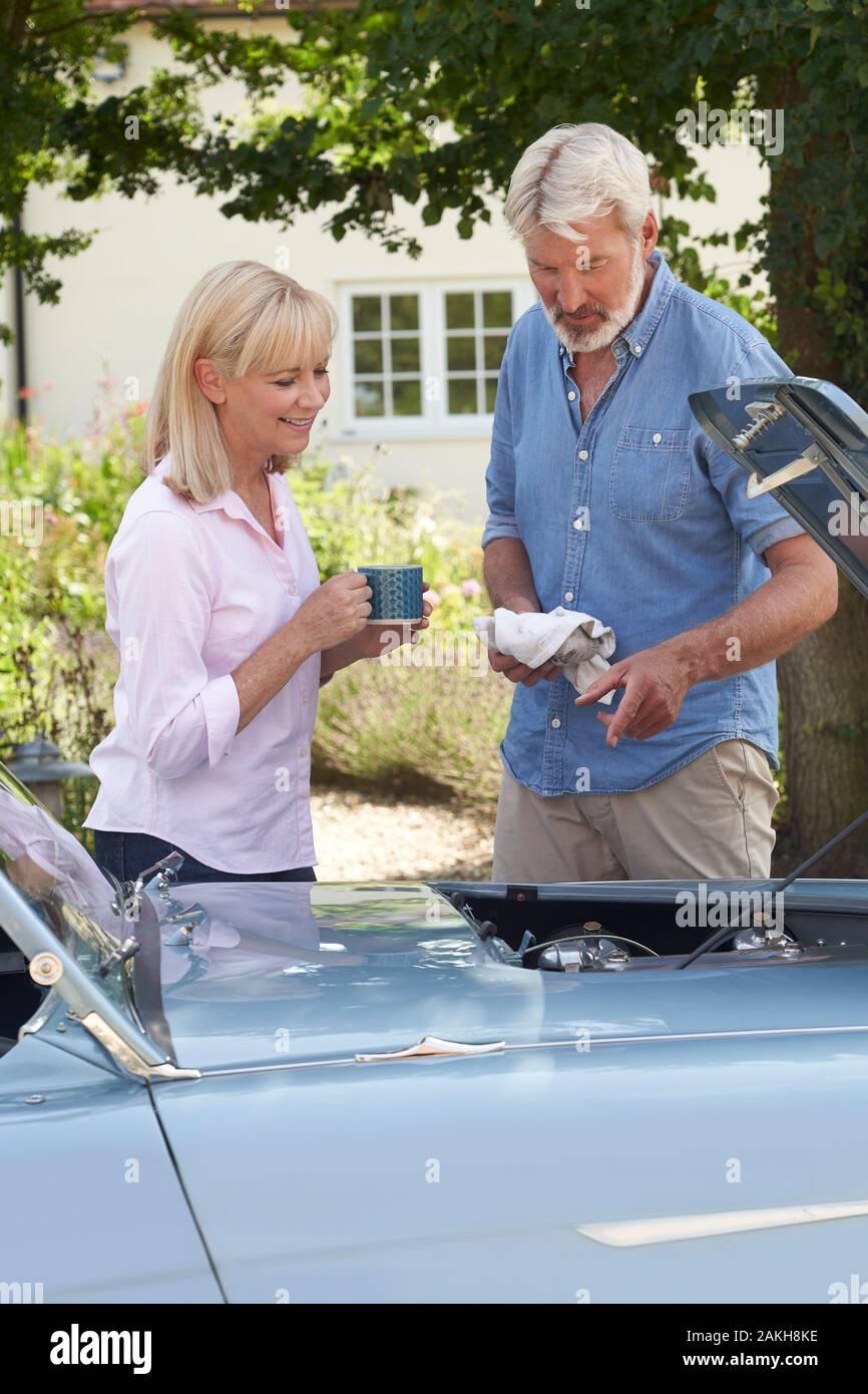 Mujer madura traer bebida caliente al hombre la restauración de coches deportivos clásicos de trabajar en el motor bajo el capó Foto de stock