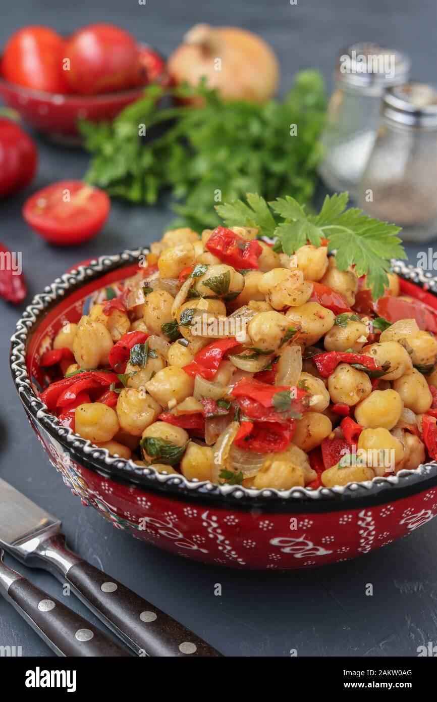 Garbanzos con guarnición de pimiento y tomate, un plato vegetariano ricos en proteína, que se encuentra en una placa contra un fondo oscuro, orientación vertical Foto de stock