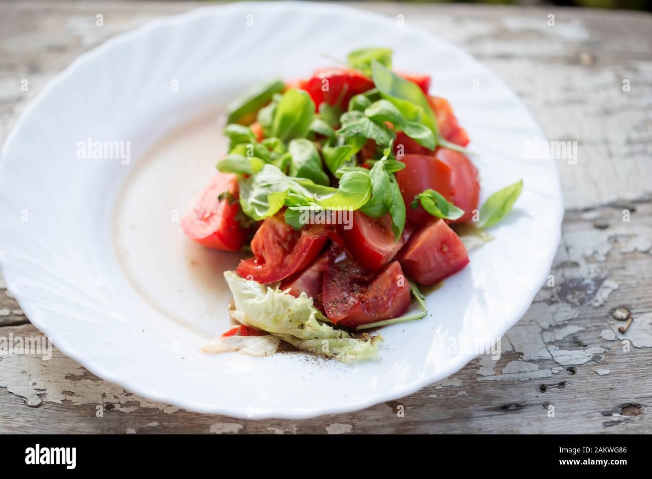 Ensalada de tomate con lechuga, albahaca y vinagreta Foto de stock