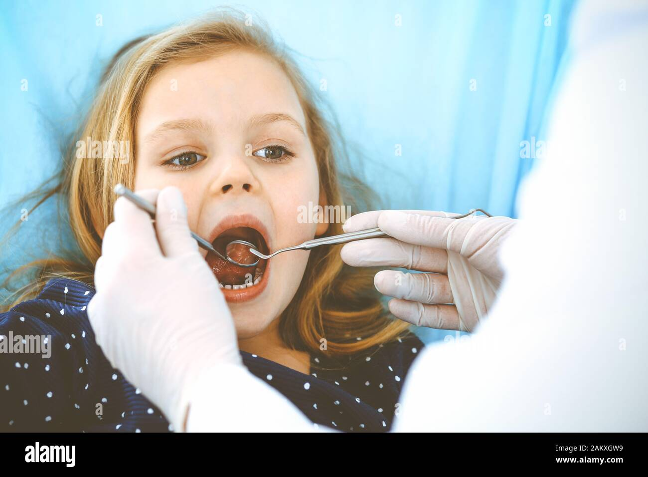 Hijita sentado en el sillón dental con la boca abierta durante la revisión oral al médico. Visitando la oficina de dentista. Concepto de medicina. Foto de tonos Foto de stock