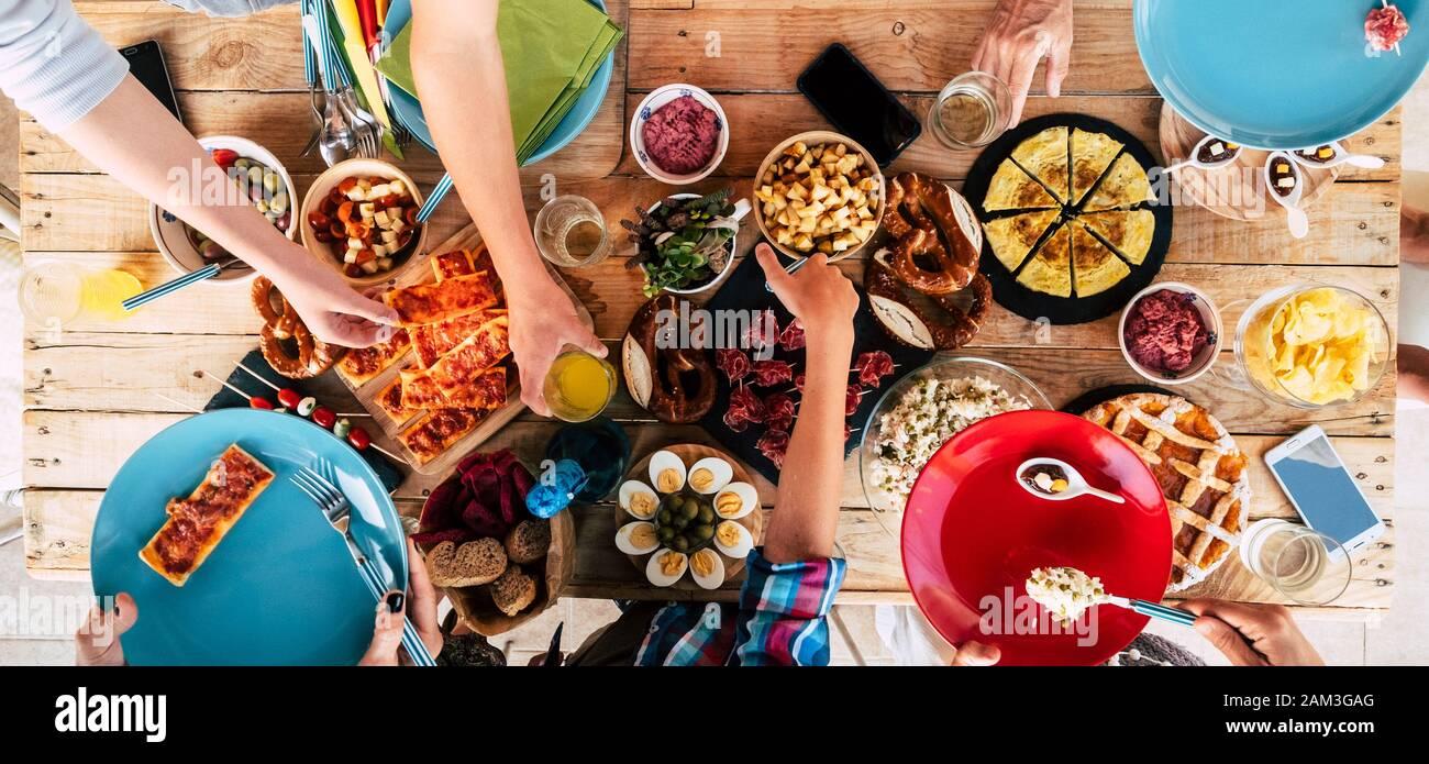 Por encima de la vista de la mesa de madera de moda llena de amigos y comida casera para celebrar y permanecer juntos teniendo diversión en la amistad - concepto de cauca Foto de stock