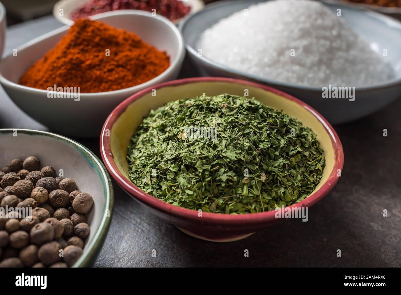 Perejil seco y especias variadas y hierbas en tazones Foto de stock