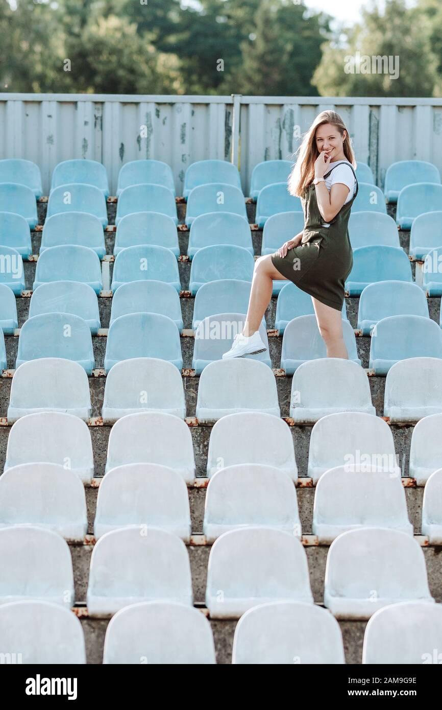 Una chica sonriente se encuentra cerca de los asientos del estadio Foto de stock
