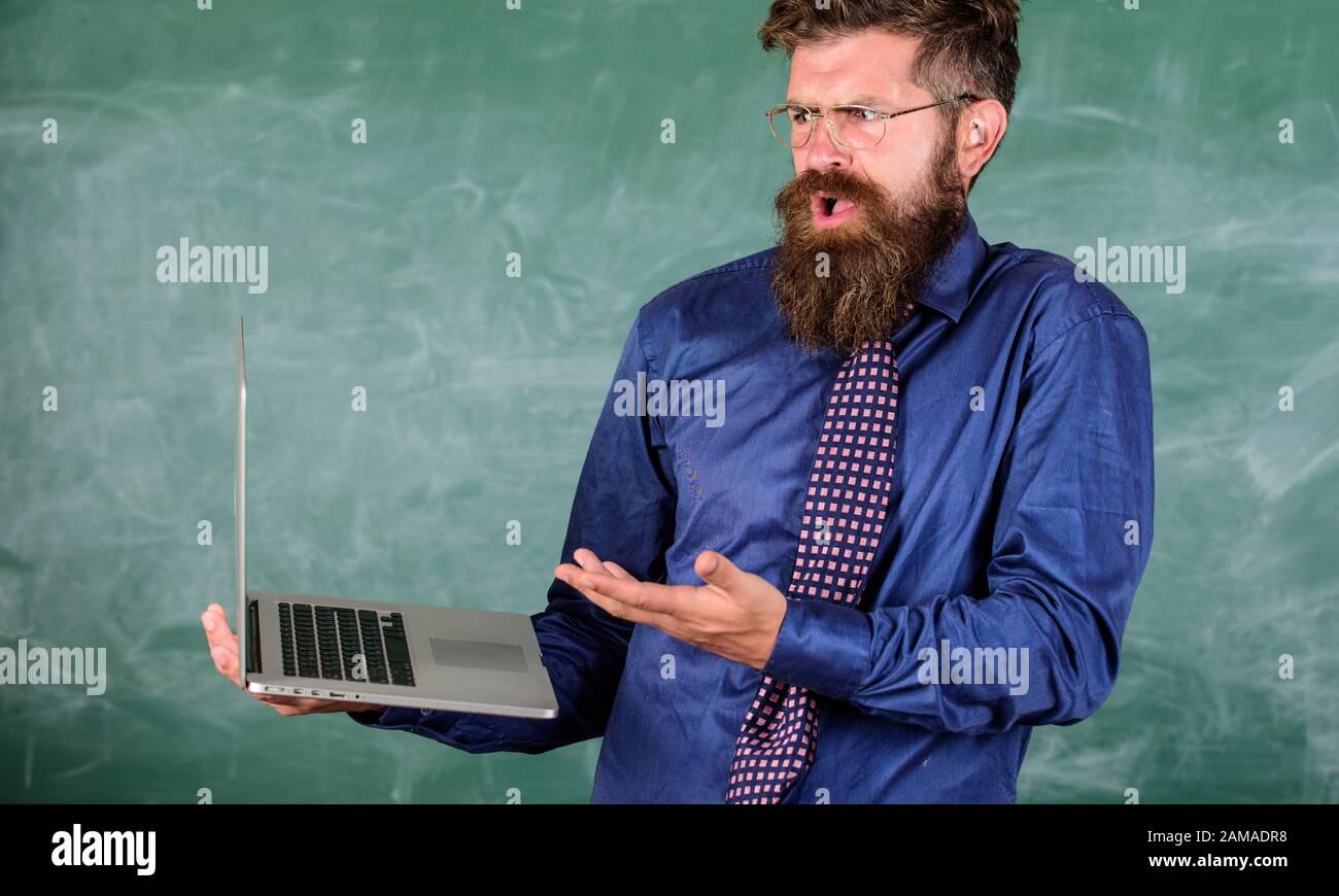 El hombre barbudo del profesor trabajo confuso con el fondo moderno de la pizarra del portátil. Hipster maestro de expresión confusa tiene portátil. Temas de educación a distancia. Temas de enseñanza utilizando tecnologías modernas. Foto de stock