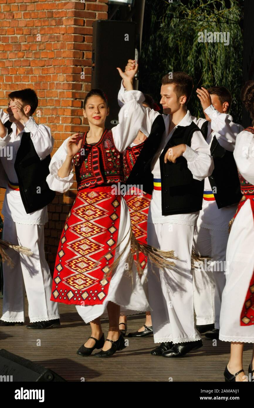 Bailarines profesionales del Banatul Folklore Ensemble tienen las manos en una danza tradicional rumana con trajes tradicionales hermosos. Foto de stock