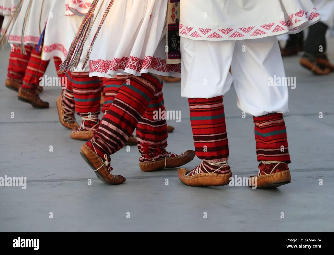 Bailarines profesionales del Timisul Folklore Ensemble tienen las manos en una danza tradicional rumana con trajes tradicionales hermosos. Foto de stock