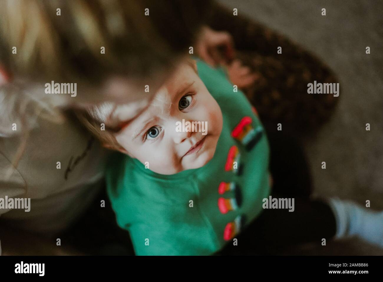 Niño pequeño sentado en el regazo de las madres Foto de stock