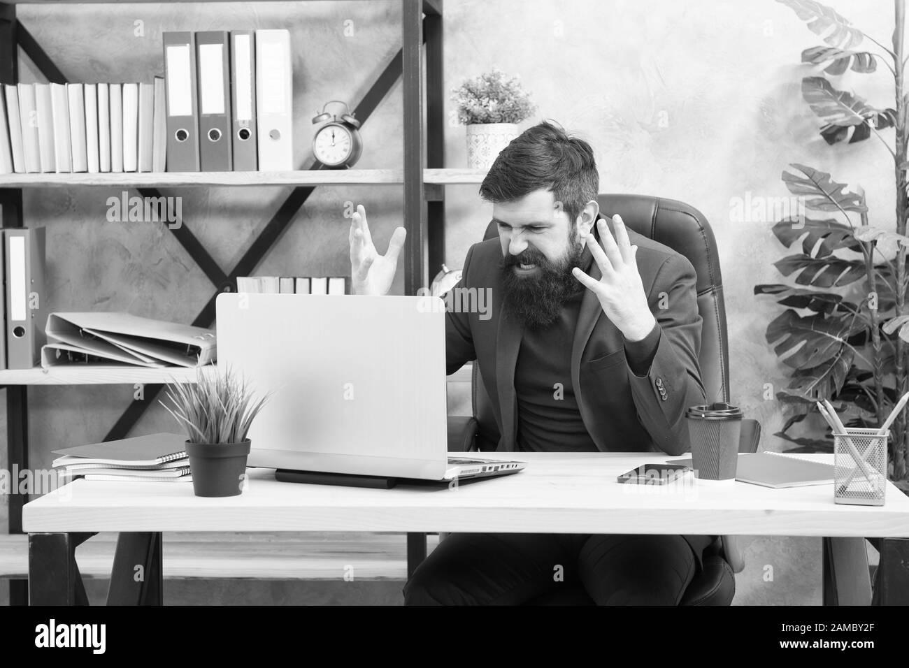 Me metí en desorden. El hombre barbado boss manager sit oficina con ordenador portátil. Manager solucionar problemas empresariales en línea. Hombre de negocios fracasado. Un negocio arriesgado. Broker y los indicadores financieros. Los precios de las acciones bursátiles. Foto de stock