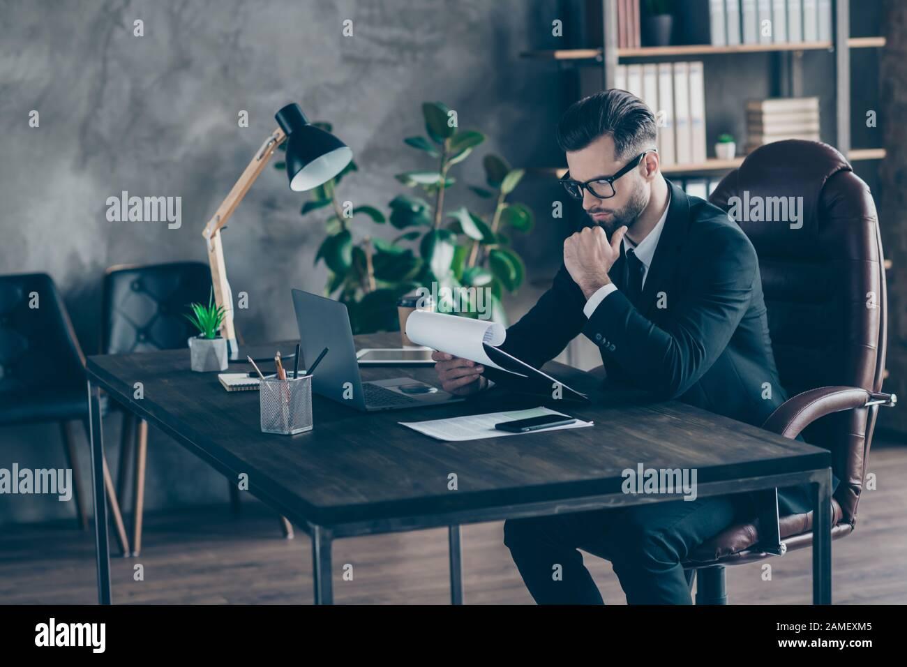Foto de perfil de guapo hombre de negocios leyendo informe de papel sujetando la mano en la barbilla considerado documentos importantes desgaste especificaciones negro blazer camisa traje Foto de stock