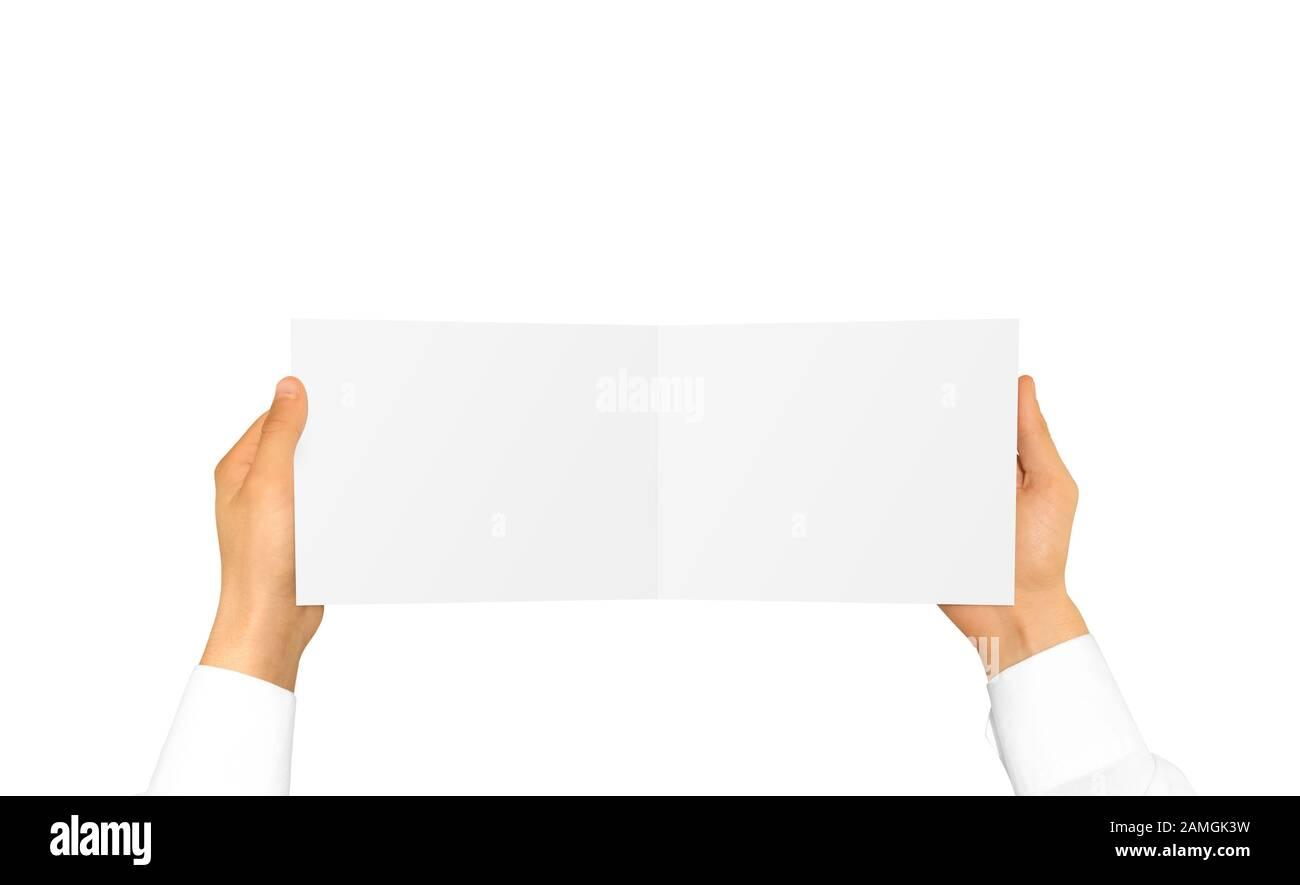 Mano en manga blanca de la camisa que sostiene la tarjeta del folleto en blanco adentro el han Foto de stock