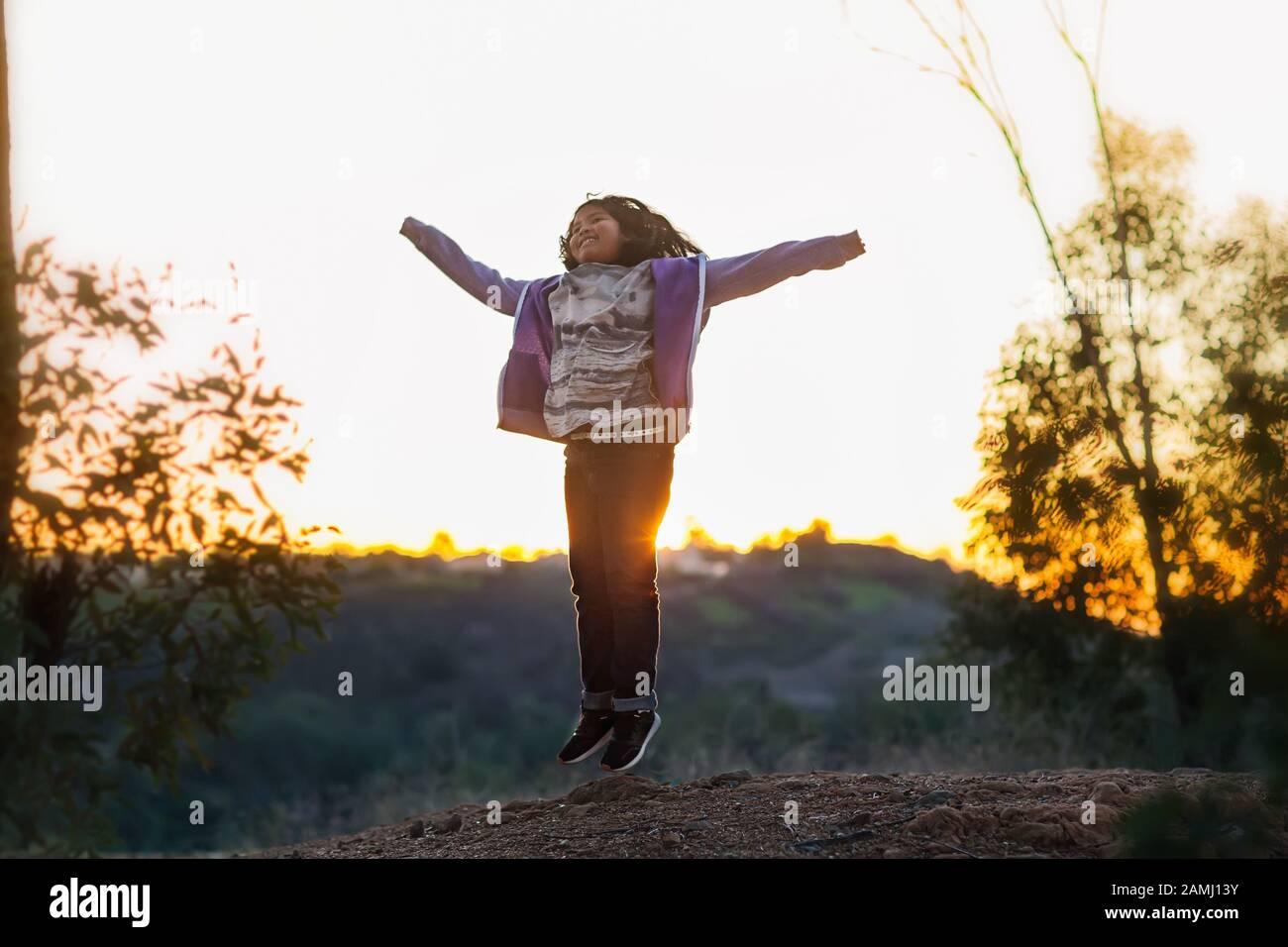 Una joven saltando con brazos arriba en la cima de una colina durante una puesta de sol. Foto de stock