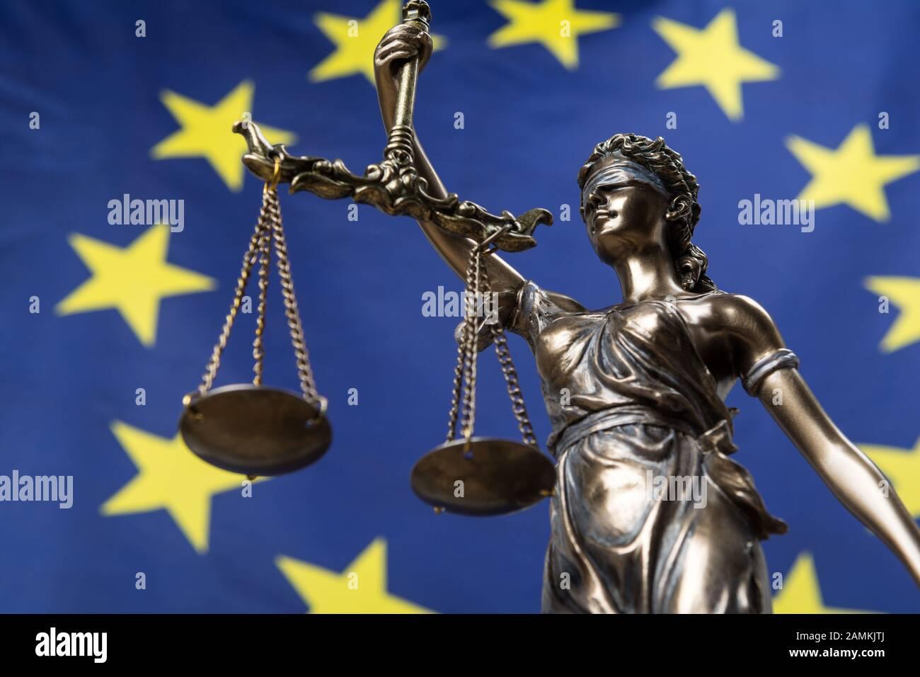 Estatua de la diosa ciega de la justicia Themis o Justitia, contra una bandera europea, como concepto legal Foto de stock