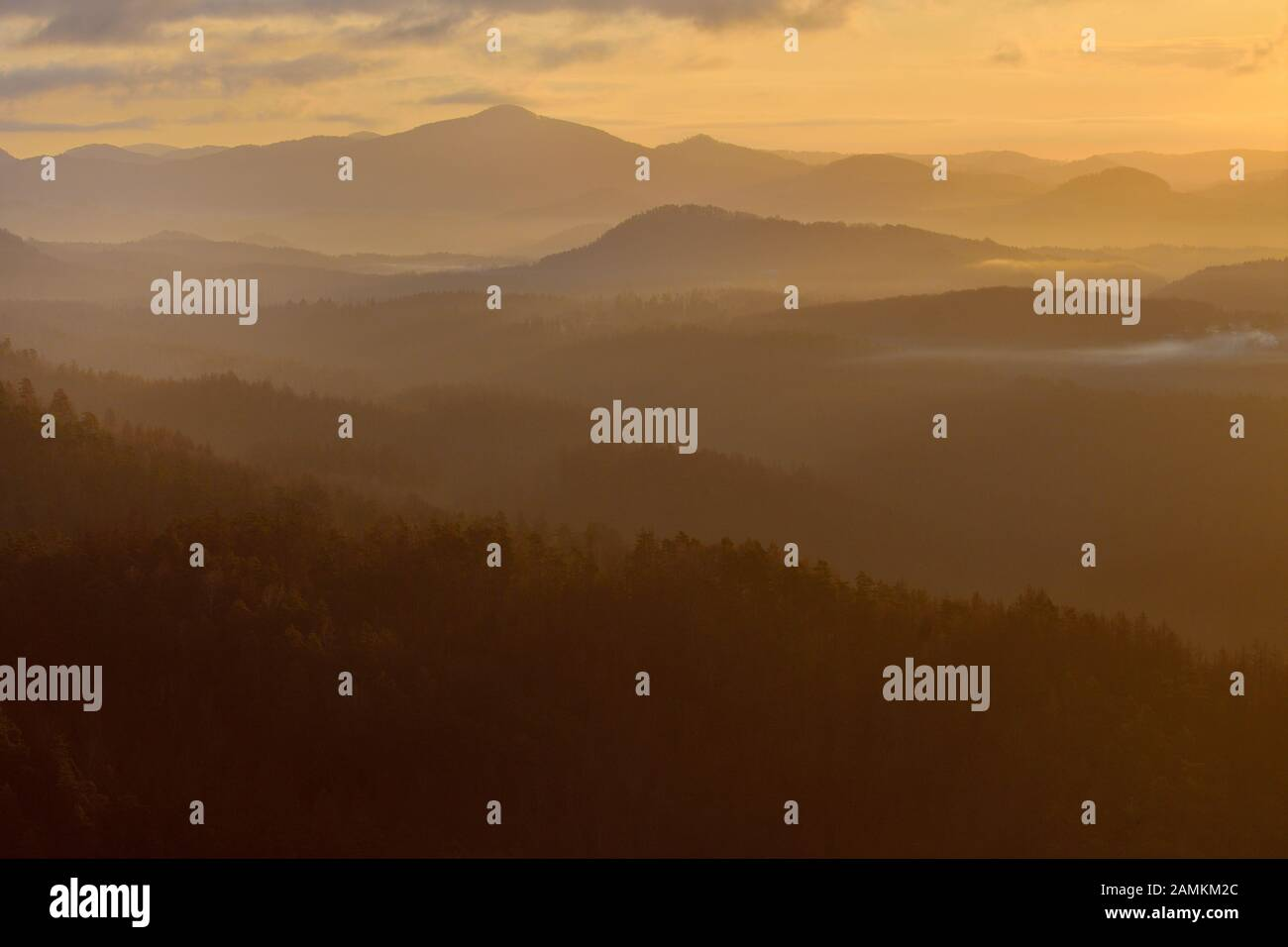 Colores anaranjados del amanecer en las montañas, niebla matutina en el valle Foto de stock