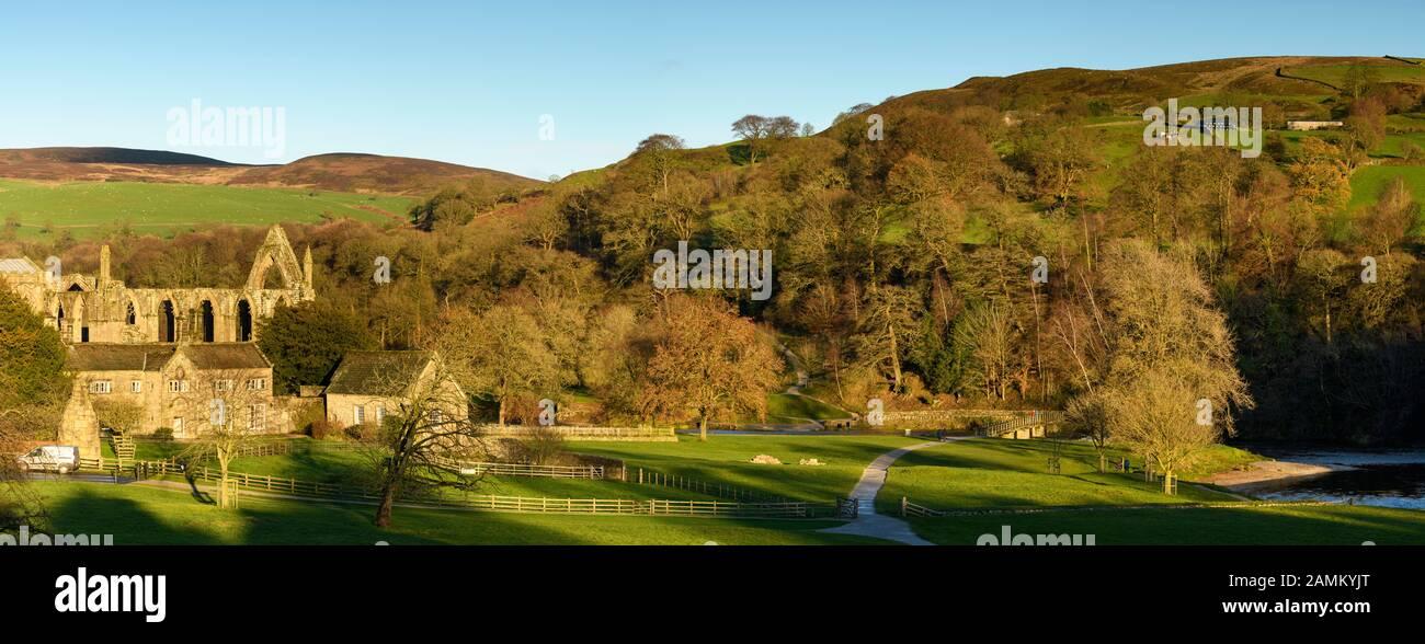 Vista rural panorámica de las antiguas y pintorescas ruinas de los prioratos monásticos, el histórico Old Rectory y las colinas iluminadas por el sol - Bolton Abbey, Yorkshire Dales, Inglaterra, Reino Unido. Foto de stock