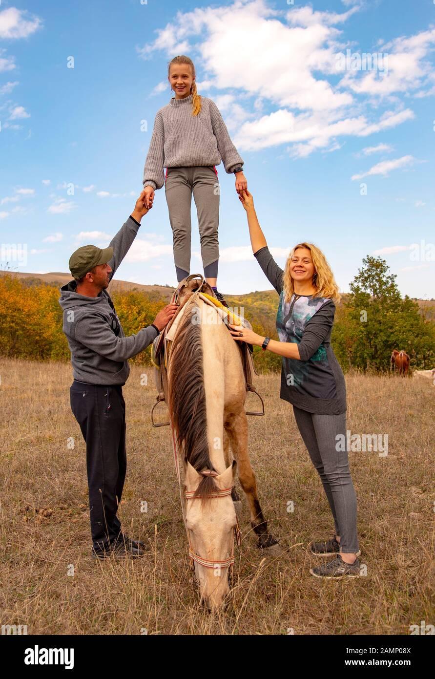 Una niña adolescente se encuentra en un caballo, apoyada por adultos a ambos lados. Foto de stock