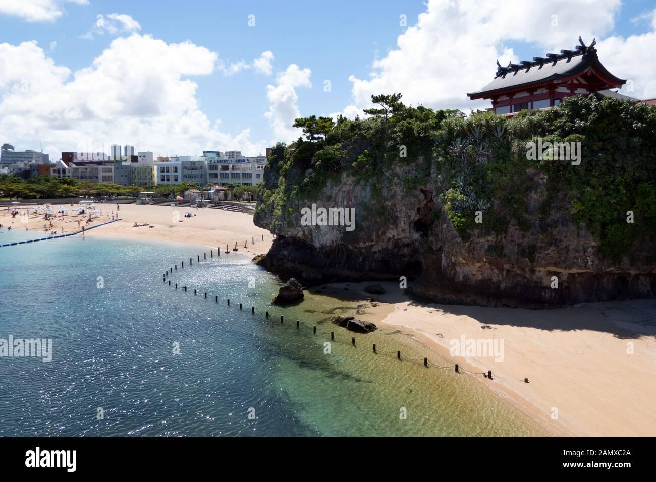 Santuario de Naminoue cerca de la playa en Naha, Okinawa, Japón, Asia. Gente japonesa nadando. Agua cristalina de mar con edificio religioso y templo Shinto Foto de stock