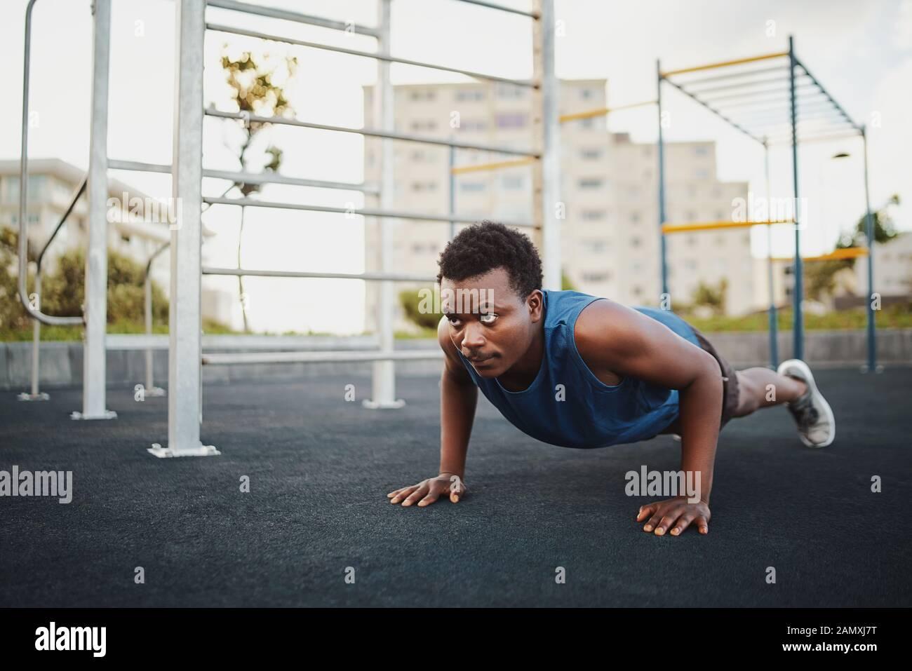 Colocar joven hombre afroamericano trabajaban sobre entrenamiento de fuerza crossfit haciendo flexiones en la calistenia park Foto de stock