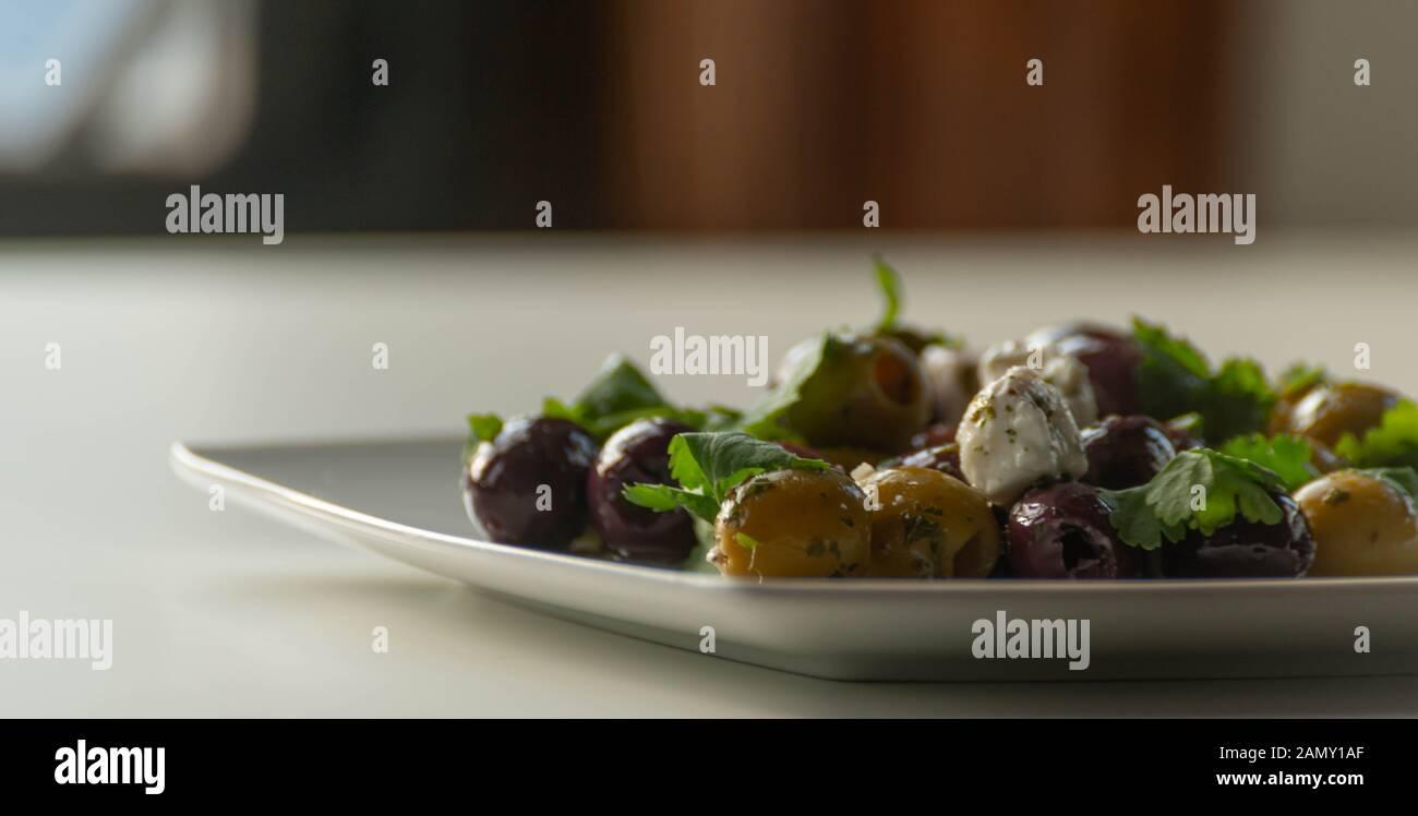Fresca ensalada griega sobre la base de aceitunas verdes y negras, con trozos de queso blanco y perejil, cocina tradicional mediterránea. Foto de stock