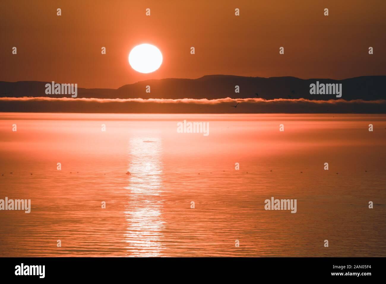 Hermosa puesta de sol con montañas y icebergs. Círculo ártico y océano. Amanecer con cielo rosa durante el sol de medianoche. Foto de stock