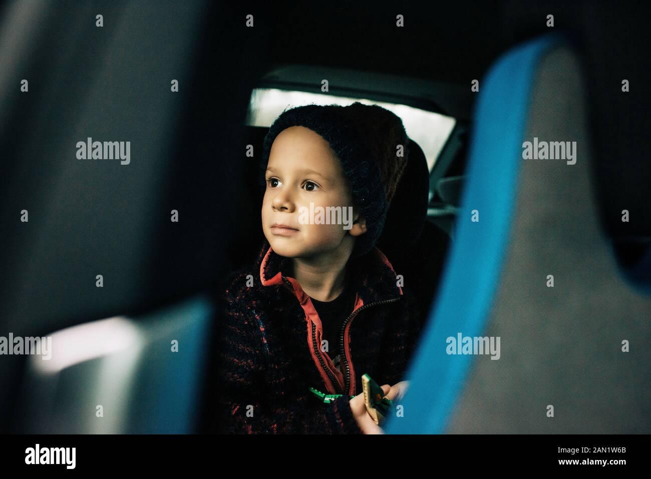 un niño se sentó en un coche eléctrico mirando por la ventana Foto de stock