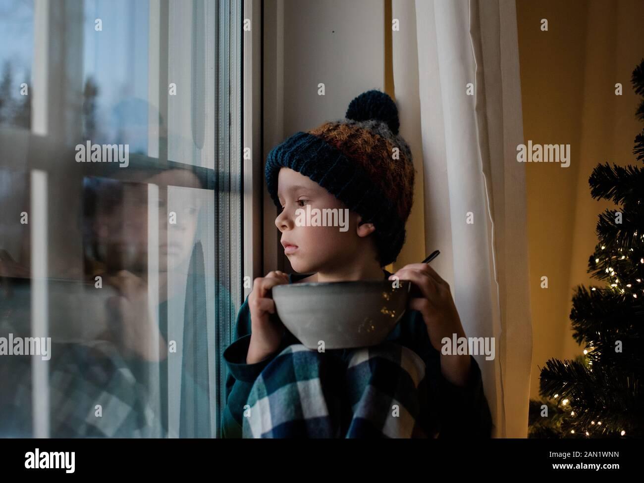 el niño se sentó en un alféizar de la ventana con un cuenco de cereales mirando hacia fuera Foto de stock