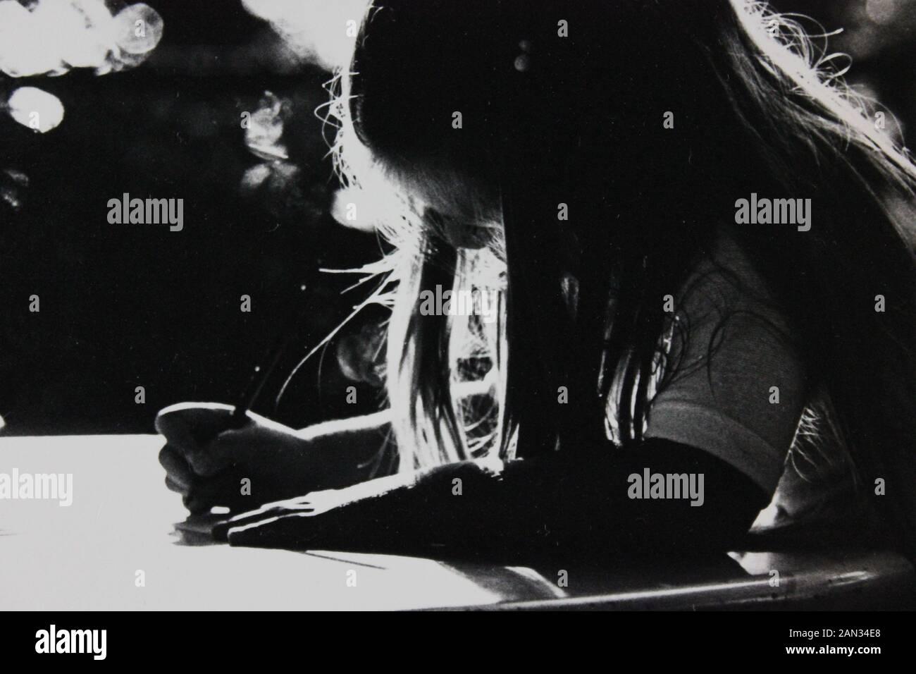 Fotografía extrema blanca y negra de los años setenta de niña escribiendo en un escritorio con retroiluminación Foto de stock