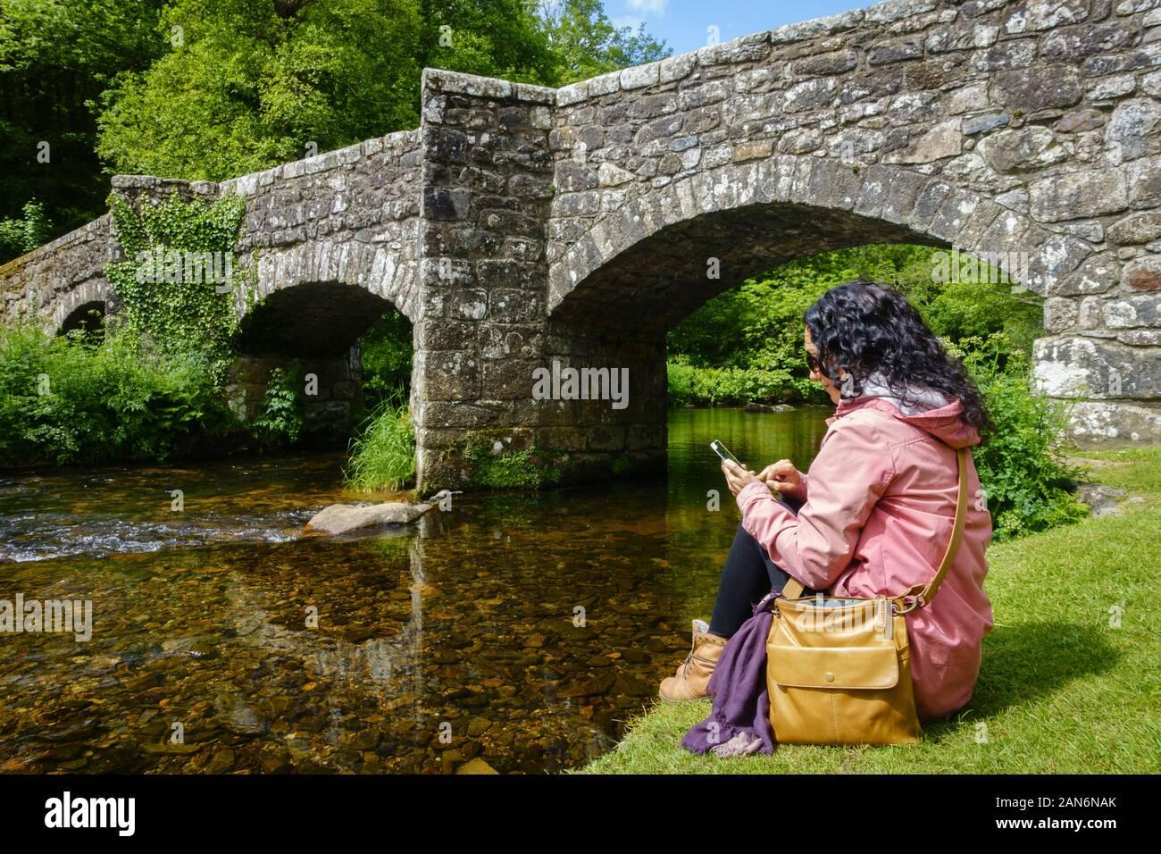 Una morena mujer blanca usando su teléfono móvil mientras está sentado por un río y antiguo puente de piedra. Siempre conectado concepto. Foto de stock