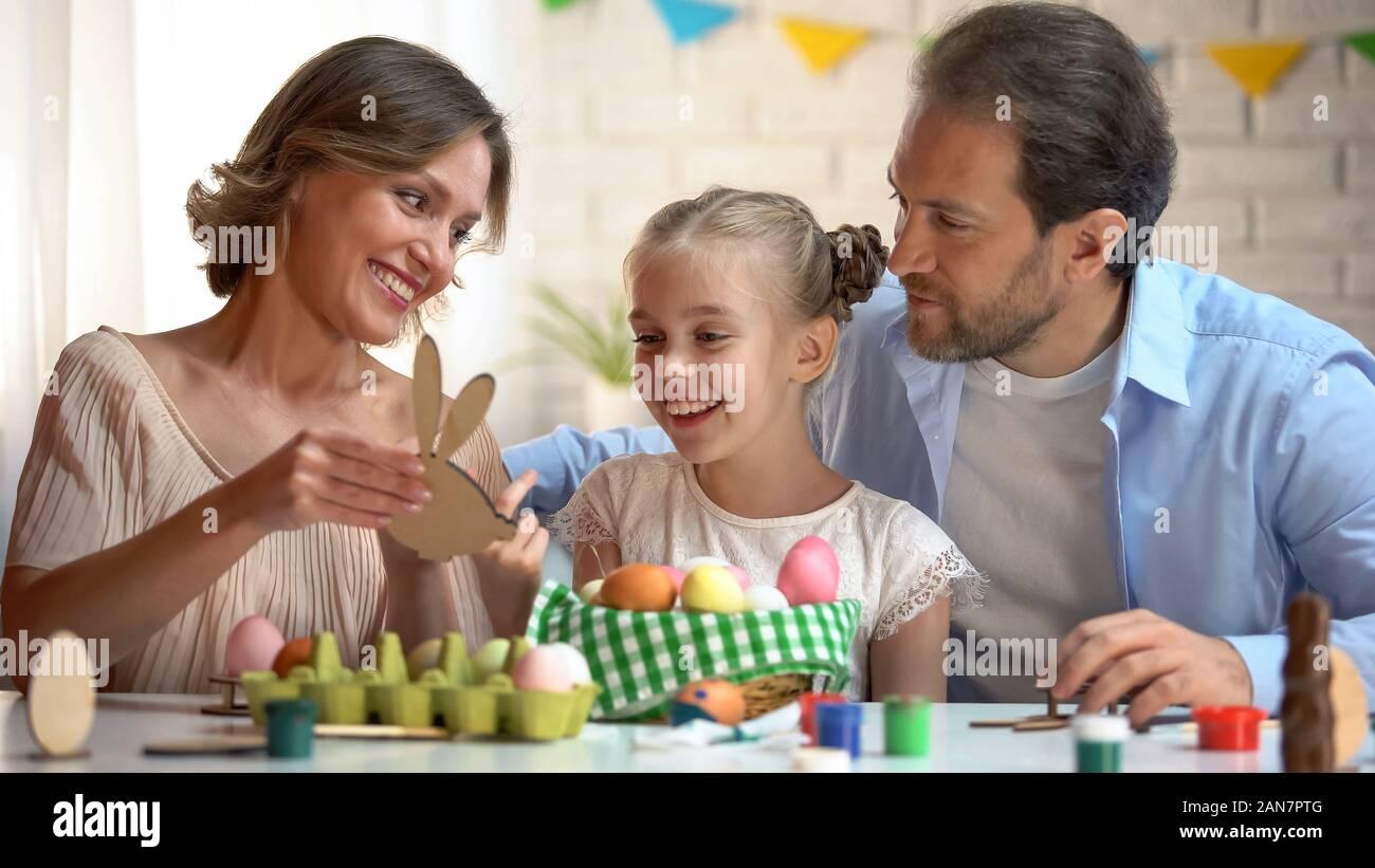 Familia admirando juguete de madera en forma de conejito de Pascua, símbolo, decoración artesanal Foto de stock