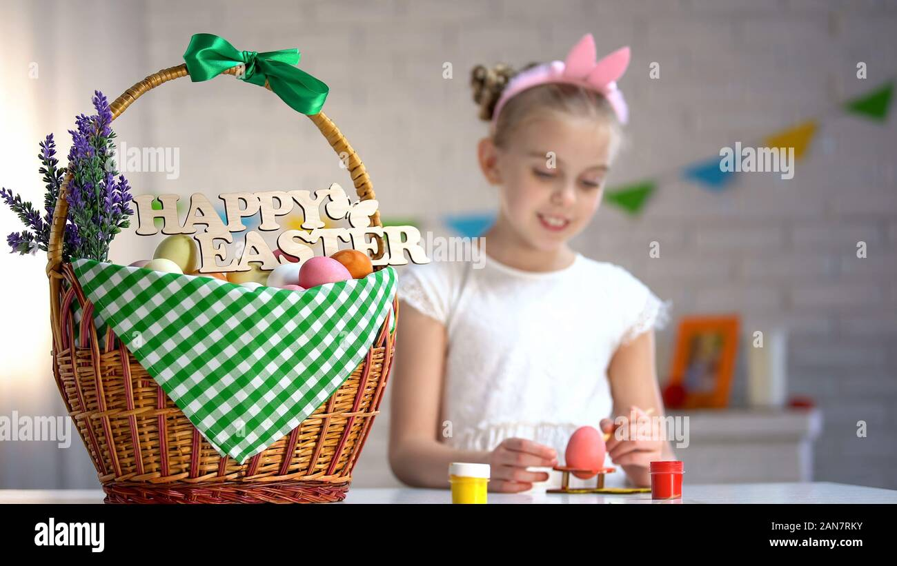 Felices Pascuas firmar en la canasta, linda chica pintando huevos sentados en la mesa, vacaciones Foto de stock