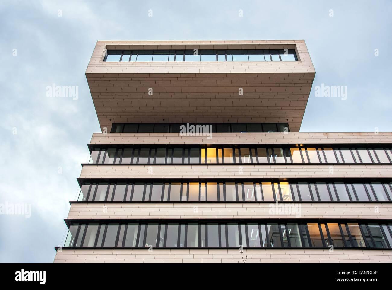 La arquitectura de diseño moderno edificio de oficinas con balcón en la parte superior, visto desde un ángulo bajo contra el cielo nublado Foto de stock