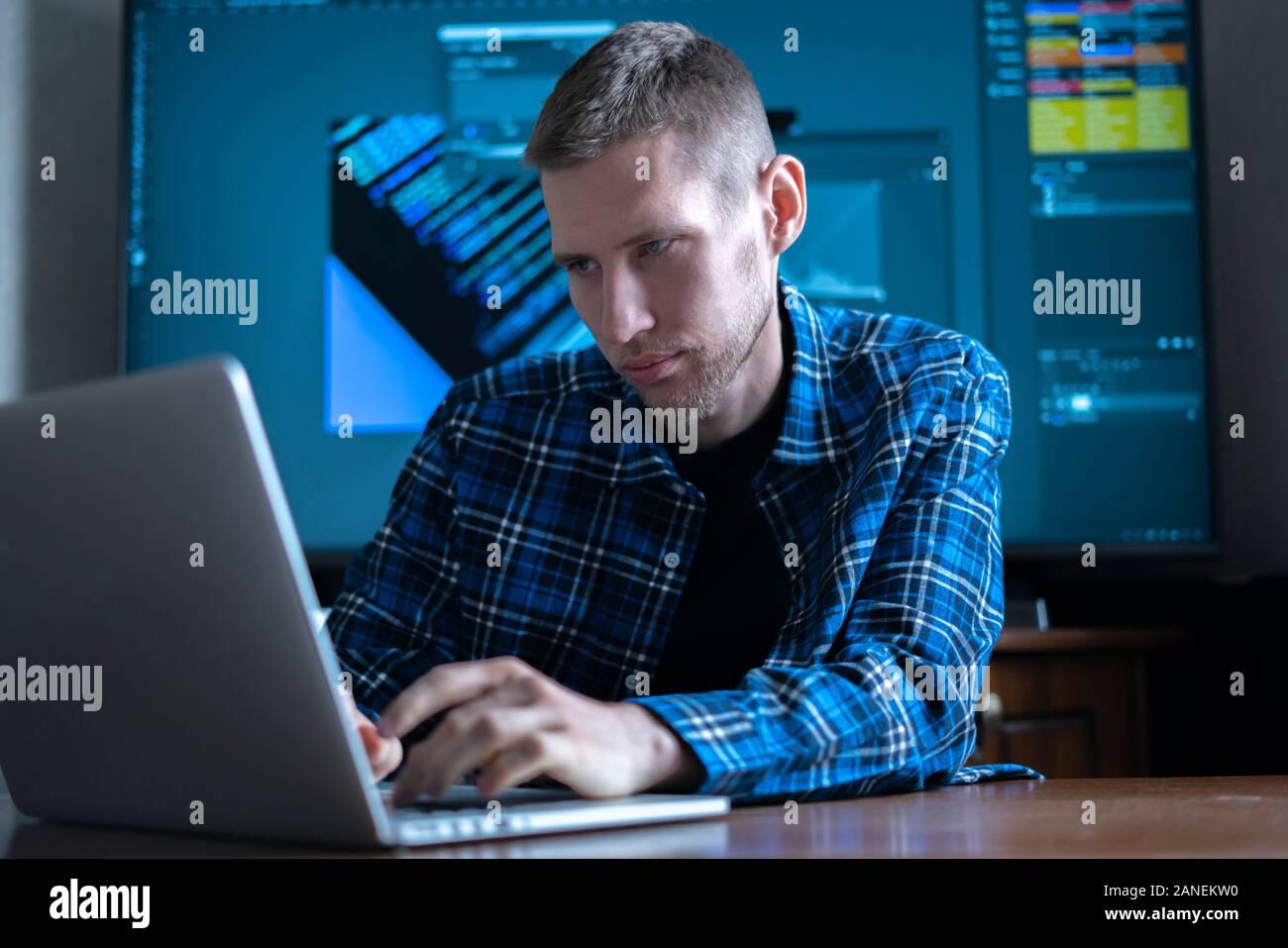 El fotógrafo masculinos sentados en la mesa trabajando en equipo, mediante la aplicación de software Foto de stock