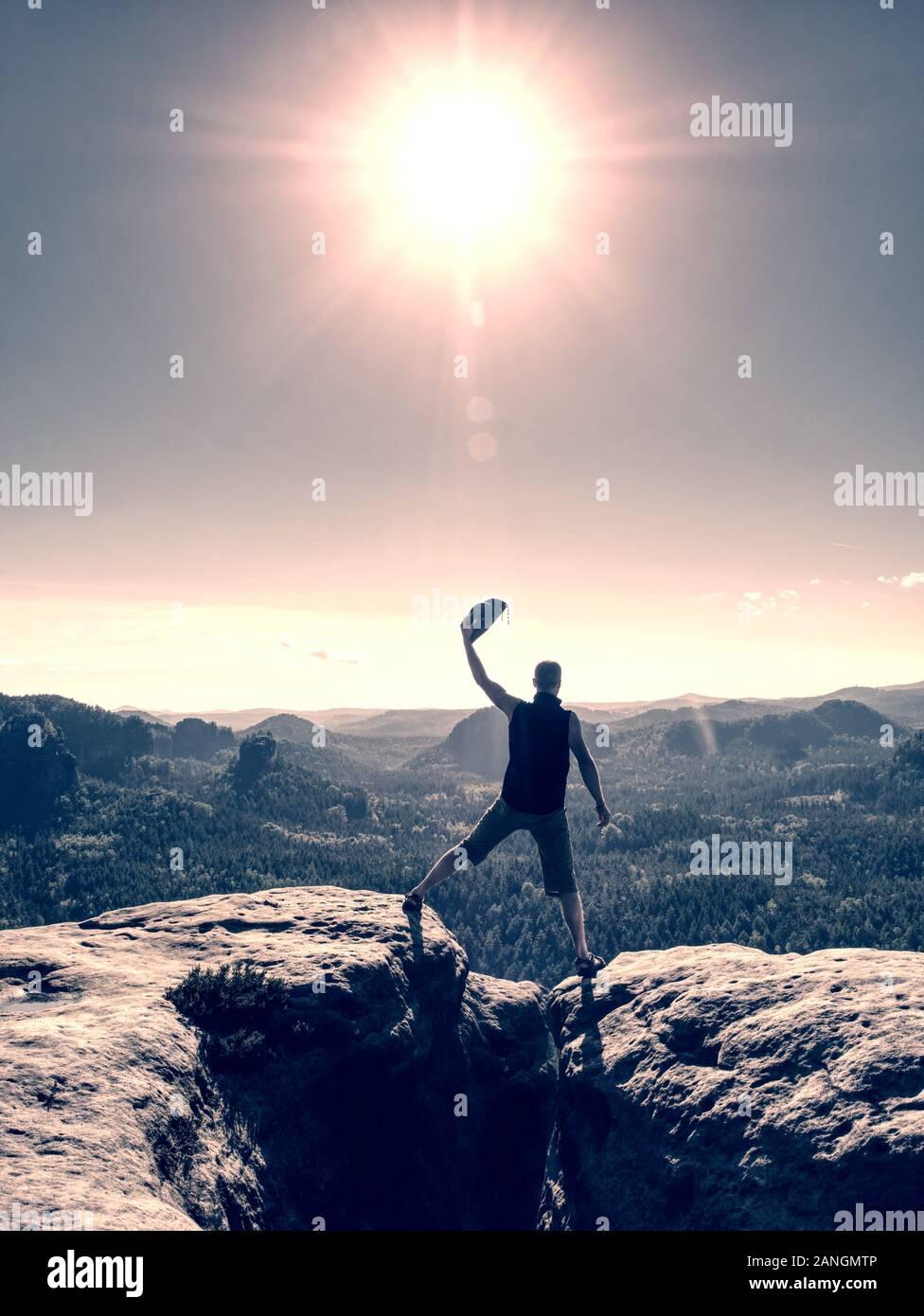 El hombre con el brazo estirado celebrando inspirador atardecer en las montañas. Macho excursionista o escalador con manos arriba disfrutar Foto de stock