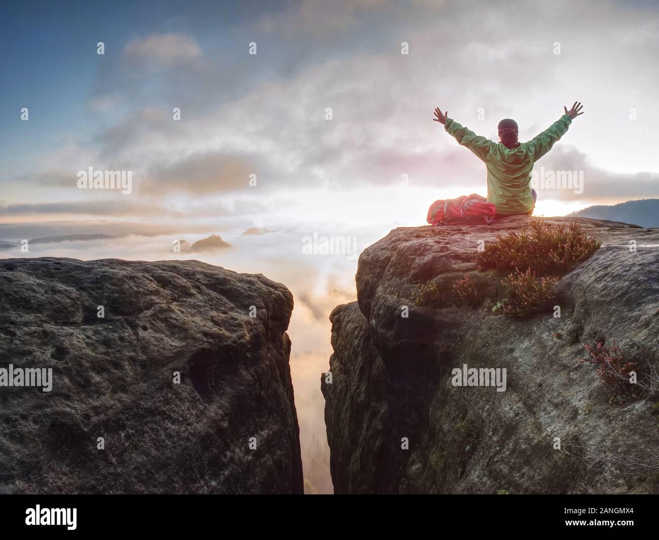 Mujer joven sentarse en la cima de una montaña, celebrar el día. Señorita caminante sentado en azul verde chaqueta con mochila roja sobre sharp cliff Foto de stock