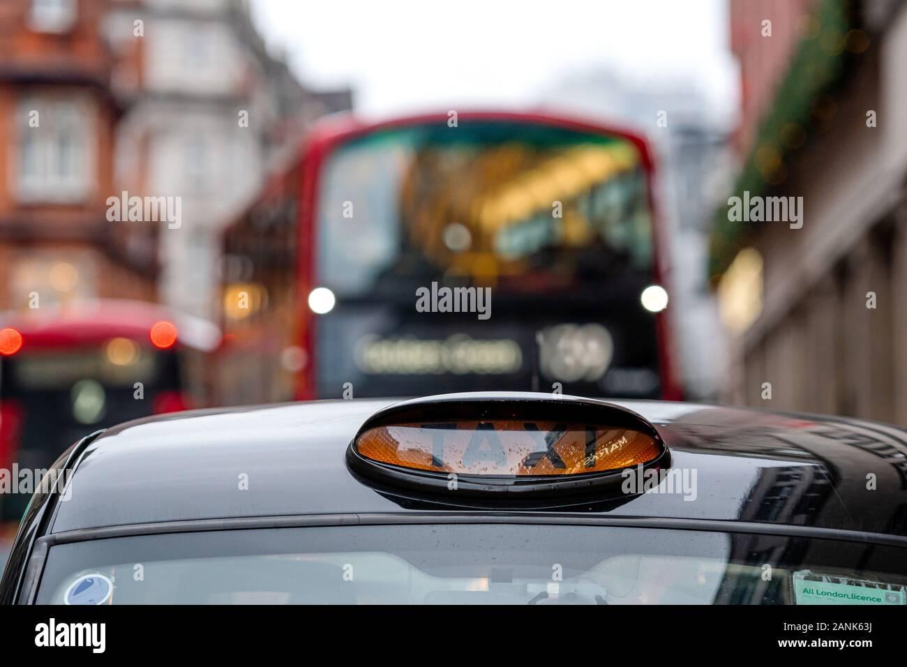 Londres, Inglaterra, Reino Unido - 31 de diciembre de 2019: un taxi negro de Londres británica firmar con autobús rojo de desenfoque de fondo - imagen Foto de stock