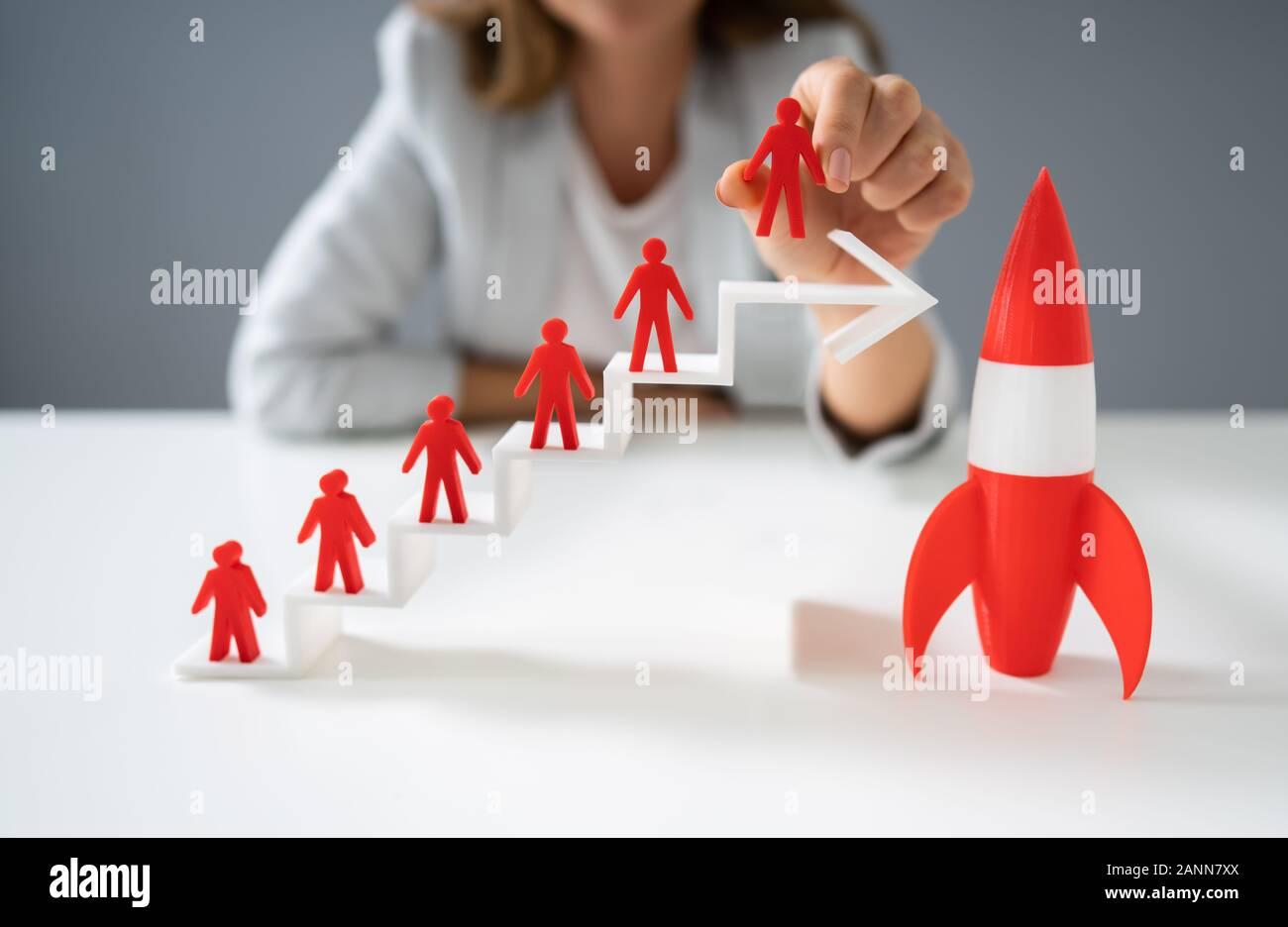 Mujer colocando rojo sobre blanco permanente de figurillas humanas crecientes gráfico de flecha cerca de la Red Rocket Foto de stock