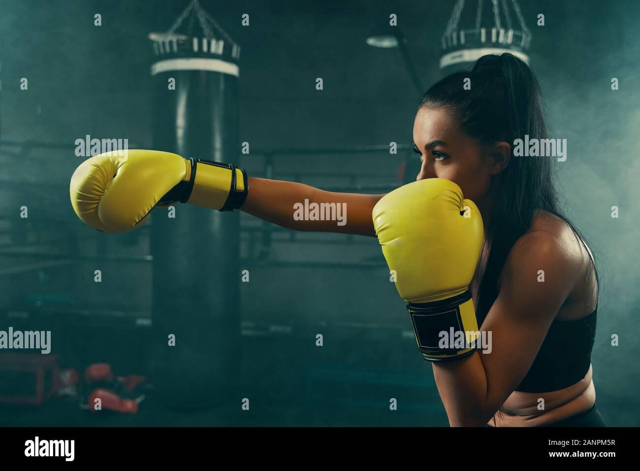 Acción de disparo joven mujer atlética entrenamiento con saco de boxeo llevaba guantes de boxeo amarillo Foto de stock