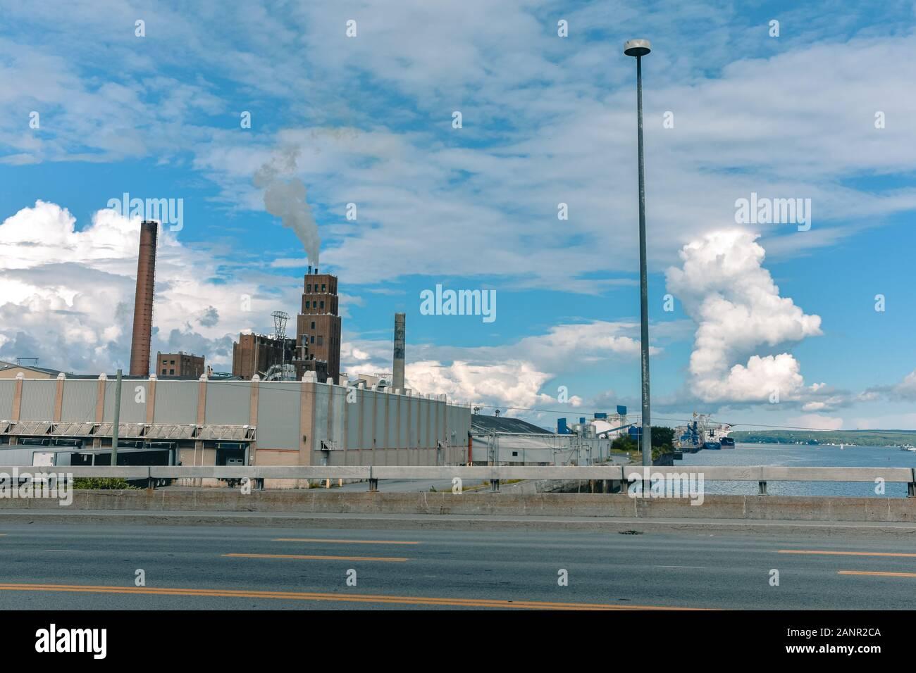Concepto de contaminación. El humo de las chimeneas, se mezcla con las nubes en un cielo azul. Canadá. Foto de stock