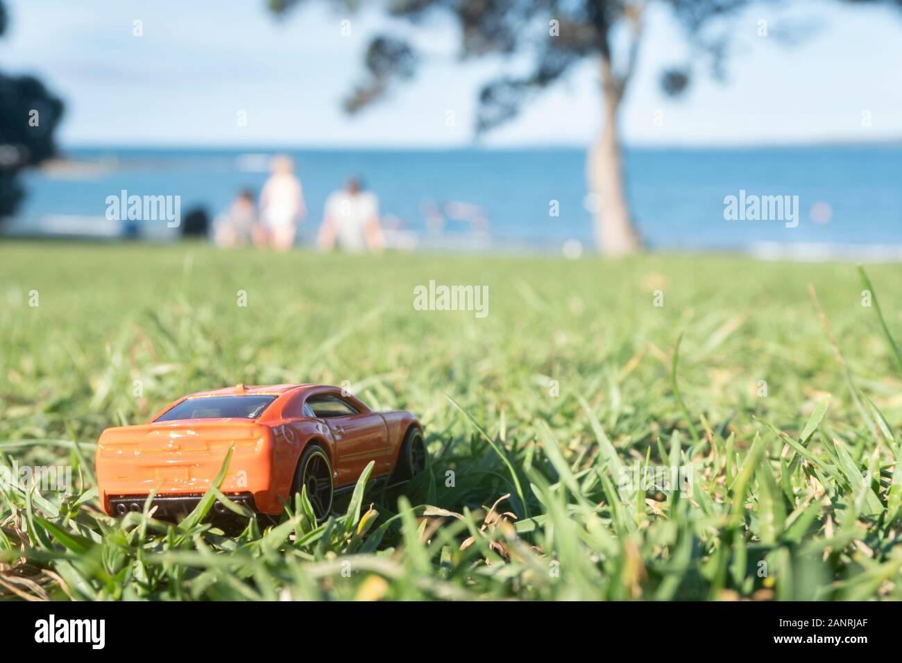 Un coche de juguete y picnic familiar en la playa - imagen de perspectiva en miniatura forzada Foto de stock