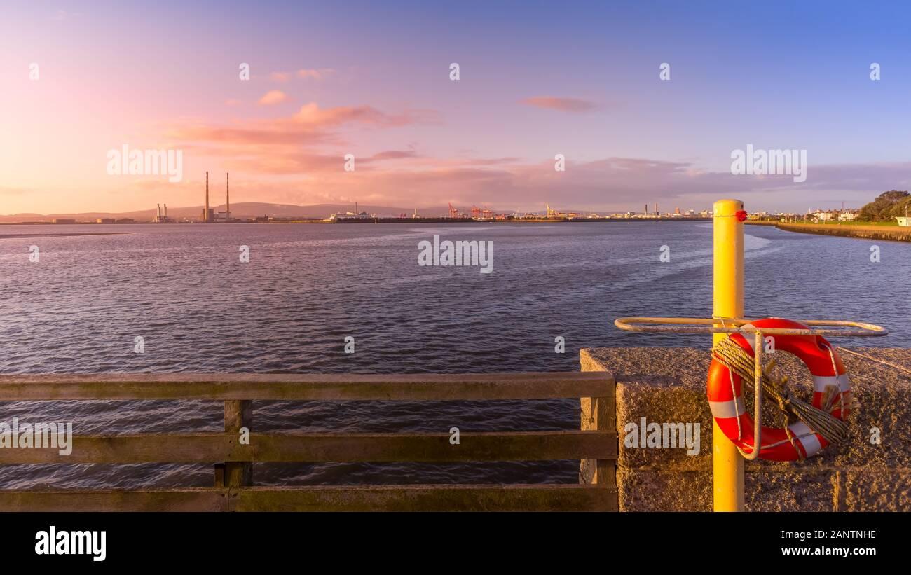 Ver en el puerto de Dublín con Poolbeg Power Plant, altas chimeneas y grúas de muelle de la isla de Toro. Salvavidas en primer plano. Increíble del amanecer, Irlanda Foto de stock