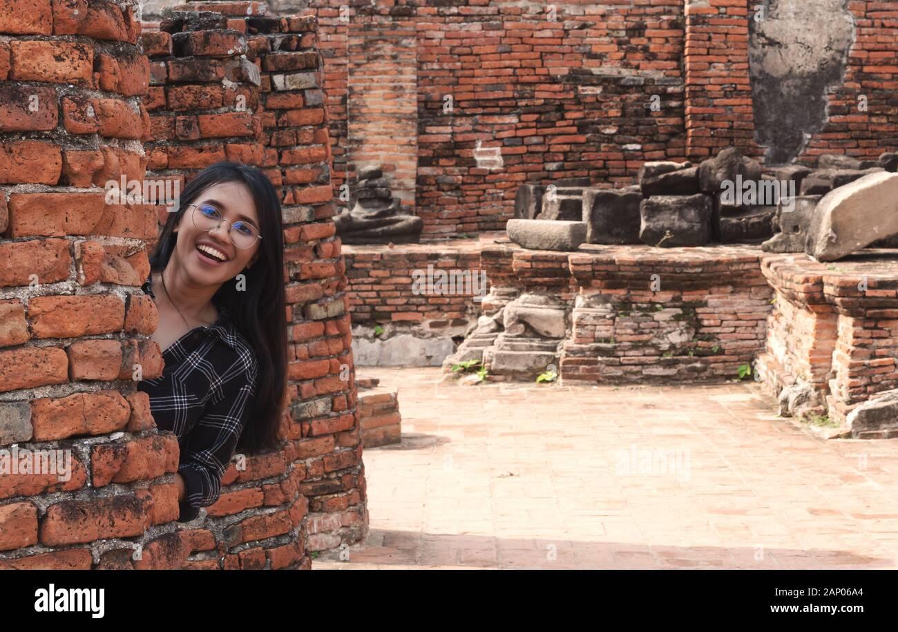 Diversión amante joven diversa niña asiática escondiéndose detrás de pared de ladrillo y sonriendo - Milennial hipster social influencer viajar a destinos turísticos culturales - viaje, tendencias y ideas de vacaciones concepto Foto de stock