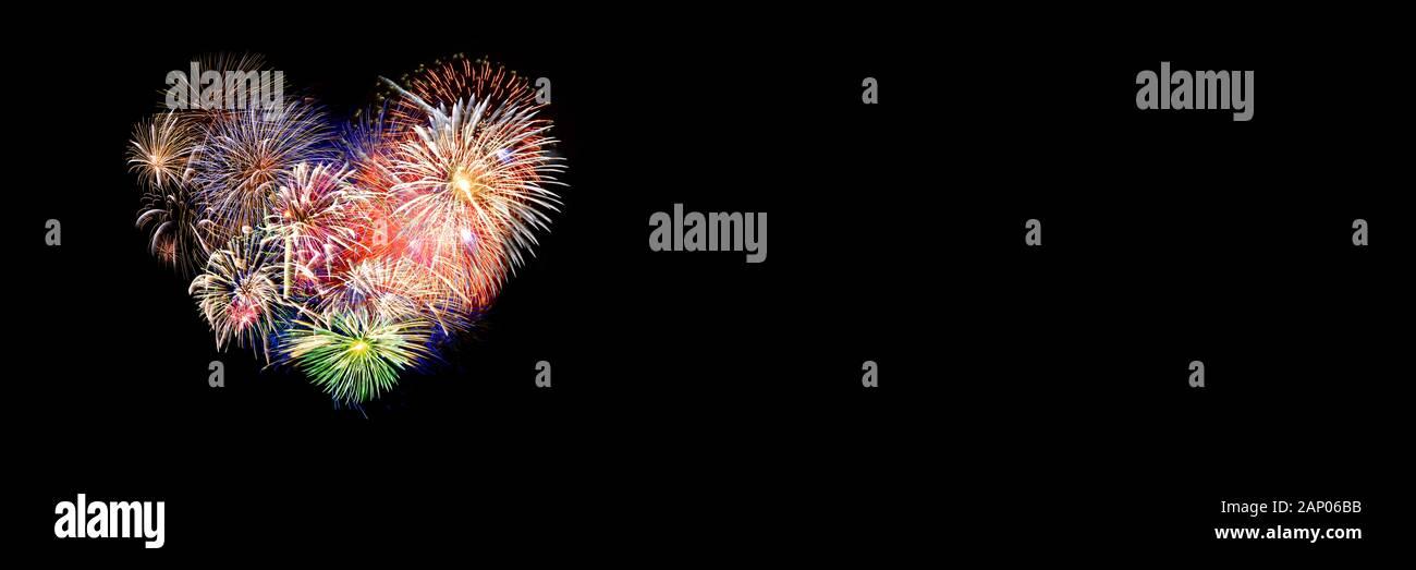 Coloridos fuegos artificiales en la forma de un corazón panorámica sobre fondo negro. Día de San Valentín banner web. Foto de stock