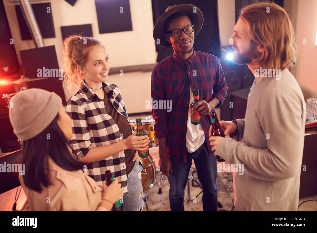 Un alto ángulo de visualización en grupo multiétnico de jóvenes bebiendo cerveza y charlar mientras disfruta de ensayo en music studio Foto de stock