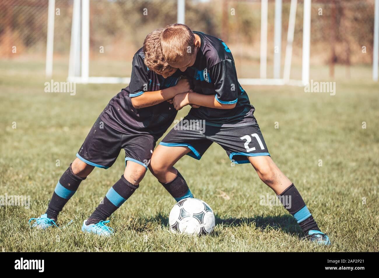 Muchachos en camisetas de fútbol patadas al fútbol en el campo de deportes Foto de stock