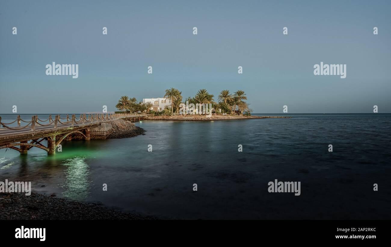 Villa Blanca en una pequeña isla con palmeras y un puente en el crepúsculo luz del atardecer, el Guna, Egipto, 07 de enero de 2020 Foto de stock