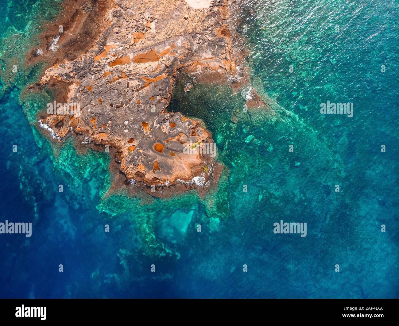 El agua clara de Azure llega a la costa rocosa de la playa de coral. Vista superior aérea Foto de stock