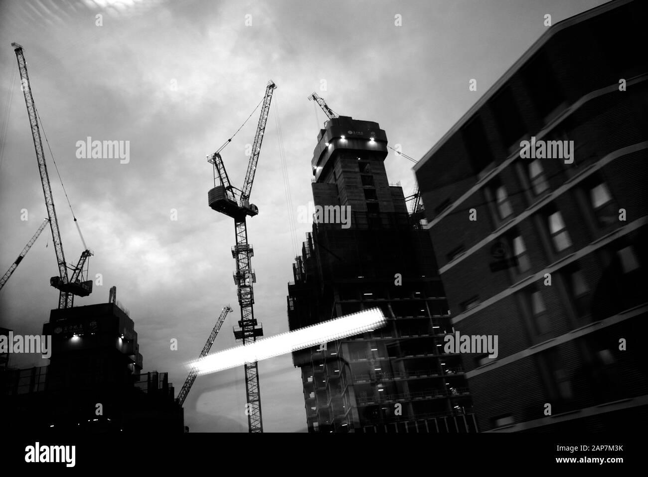 Tower Cranes visto desde y a través de la ventana de un tren en movimiento que llega a la estación de tren de Waterloo en Londres con reflejos luminosos en el cristal Foto de stock