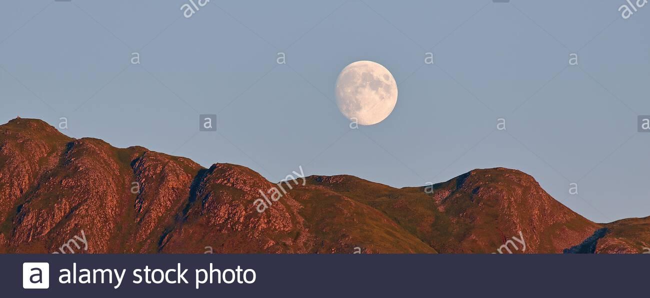 La luna llena se eleva sobre las montañas en las tierras altas escocesas Foto de stock