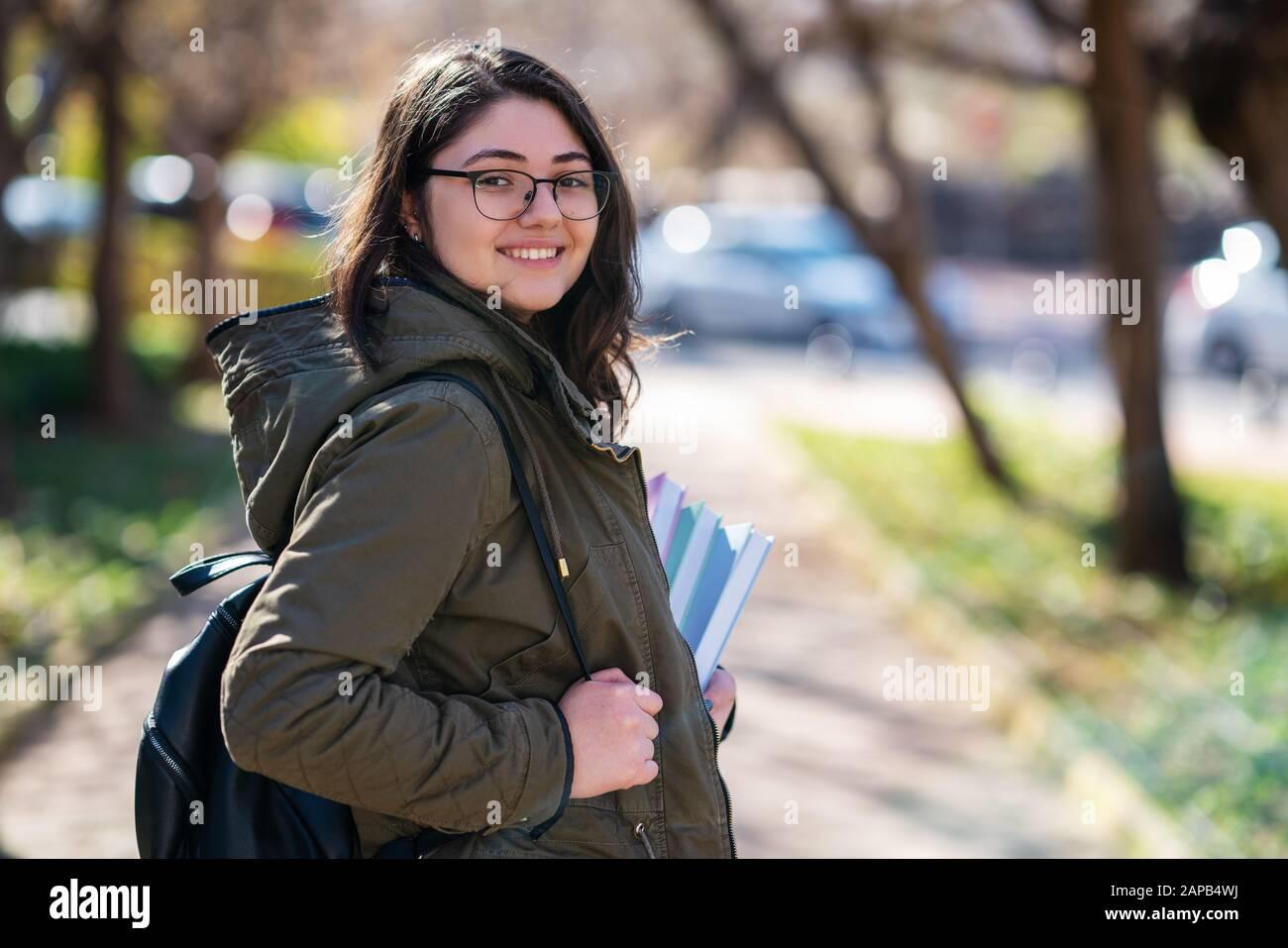 La joven intelectual se queda y mira a alguien en un parque con algunos libros en sus manos Foto de stock